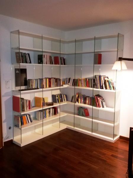 Libreria con mensole in legno e laterali in vetro trasparente.